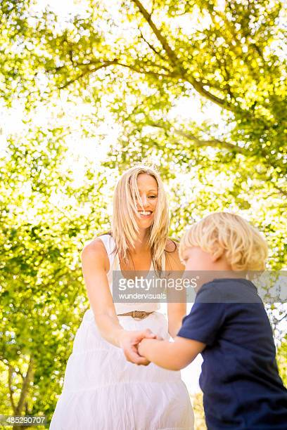 Mom and son dancing in park