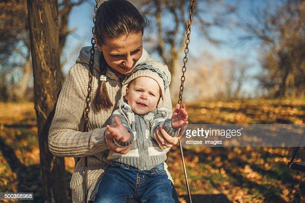 Mom and son on swing in park