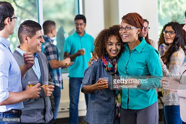 Mom and teen daughter meeting school faculty during event