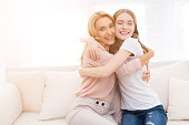 Mom and teenage daughter embrace. They are sitting on the couch at home. They are in a good mood. They are happy with each other.