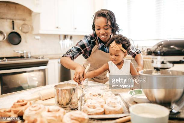 Mom and toddler baking together