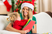 Mom and toddler daughter read books at Christmastime
