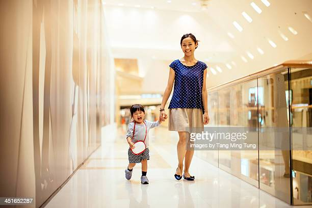 Mom and toddler girl walking in shopping mall