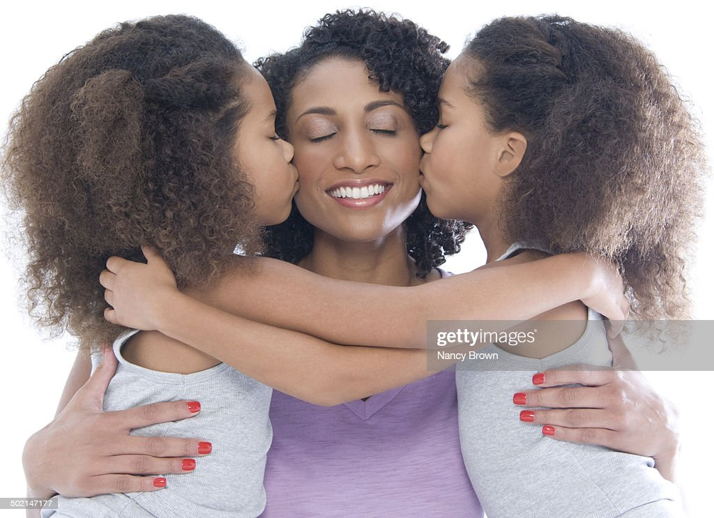 Mom and twin daughters kissing : Stock Photo