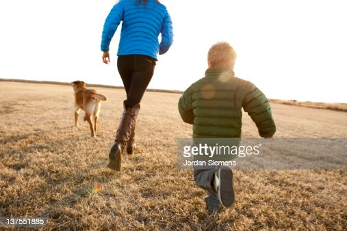 Mom and young boy running with their dog.