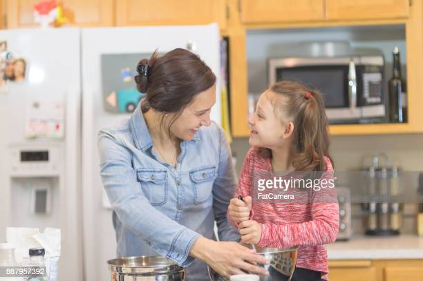 Mom and young daughter baking together in modern kitchen