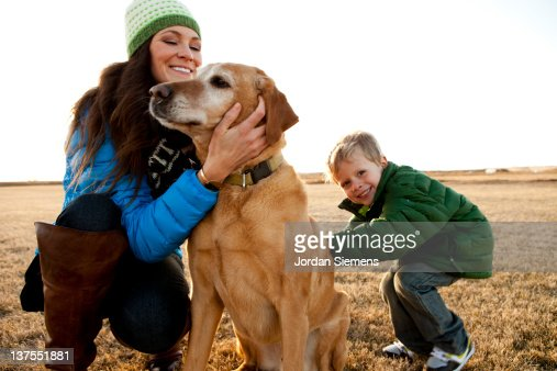 Mom and young son petting their dog. : Stock Photo