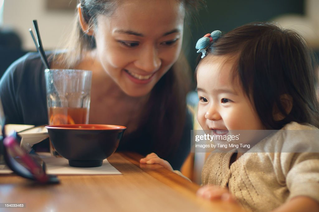 mom & baby looking at smartphone on dinning table : Stock Photo