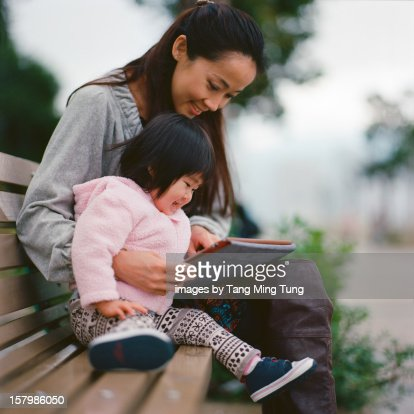 Mom & Baby playing with tablet in a park joyfully : Foto de stock