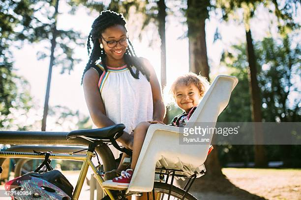 Mom Buckles Up Daughter in Bike