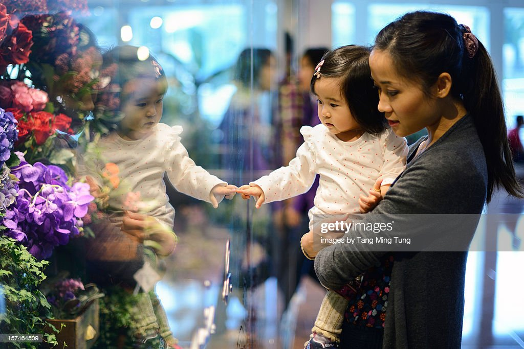 Mom carrying baby shopping for flowers in a mall : Stock Photo