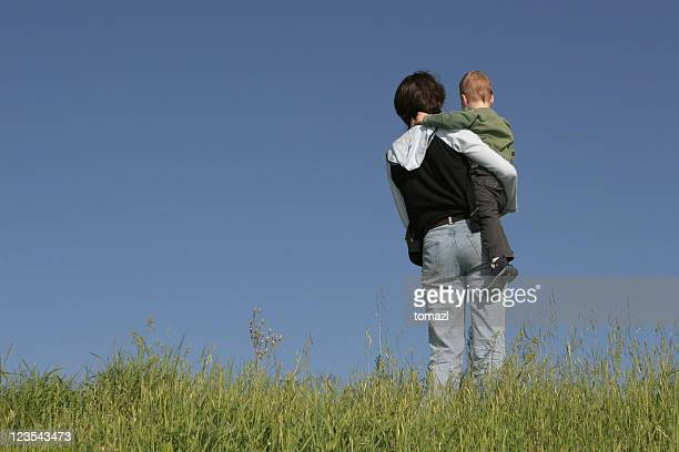 Mom carrying her son to the top of a grassy hill