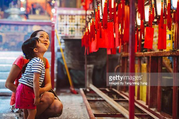 Mom & child admiring lanterns in Chinese temple