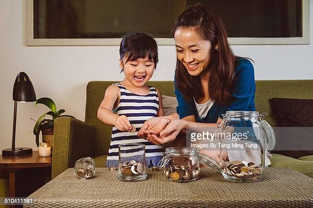 Mom & child putting coins into glass jars