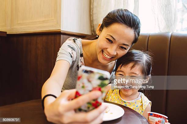 Mom & child taking selfie joyfully in cafe