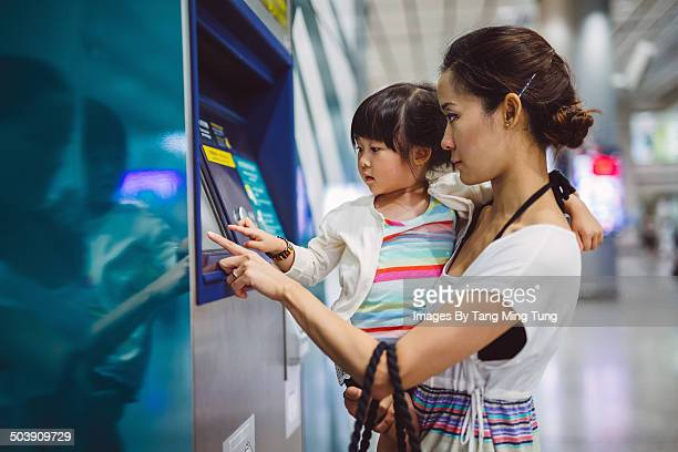 Mom & child using ATM in train station