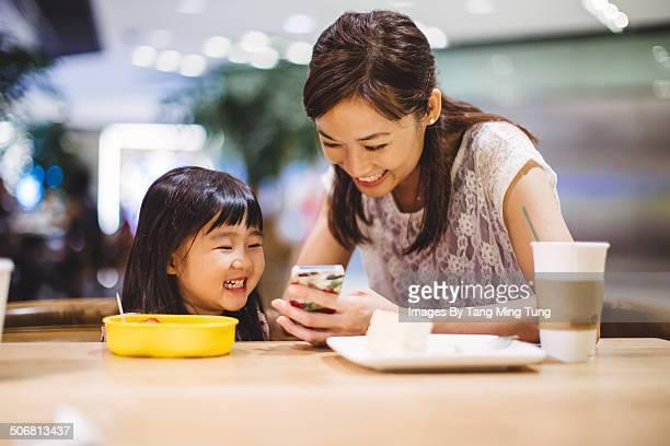 Mom & child using smartphone joyfully in cafe