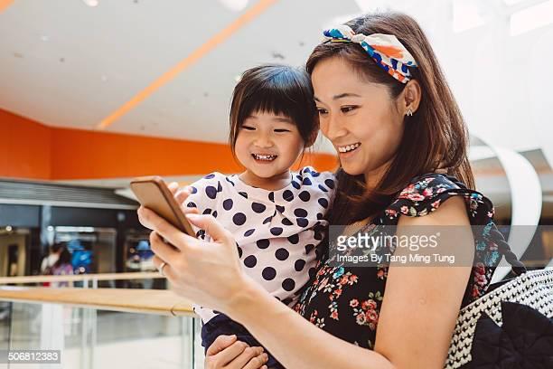 Mom & child using smartphone joyfully