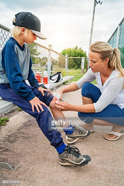 Mom cleaning son scraped knee on baseball bench.