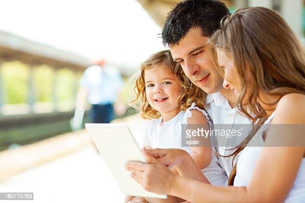 Mom, dad and little girl wait for train