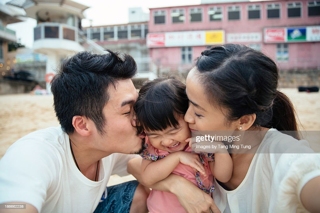 Mom & dad kissing lovely toddler girl's cheek : Stock Photo