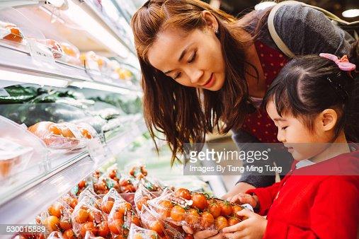 Mom & daughter choosing tomatoes in supermarket