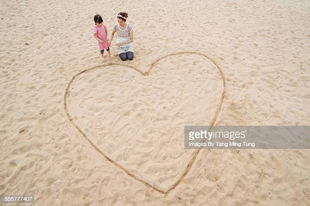 Mom & daughter drawing on sand at beach