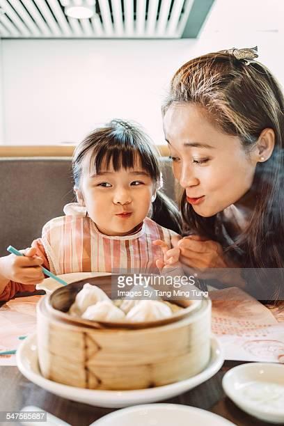 Mom & daughter enjoying Chinese dim sum dumplings