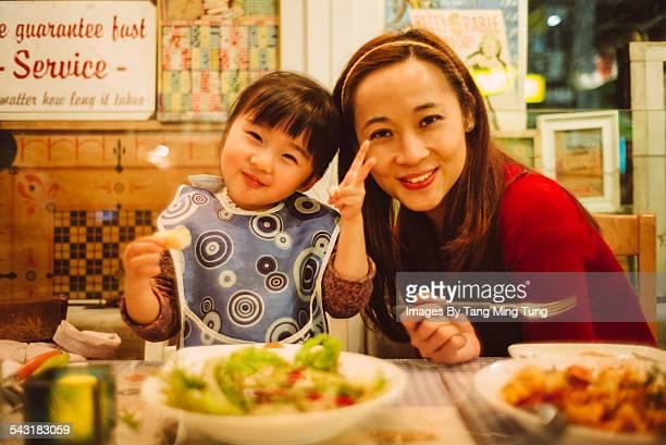 Mom & daughter enjoying meal in restaurant