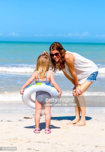 Mom daughter having fun on beach