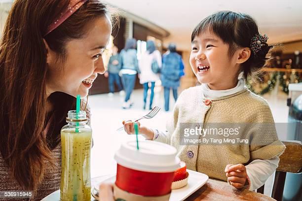 Mom & daughter having snacks in cafe joyfully