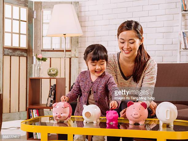 Mom & daughter inserting coins in piggy banks