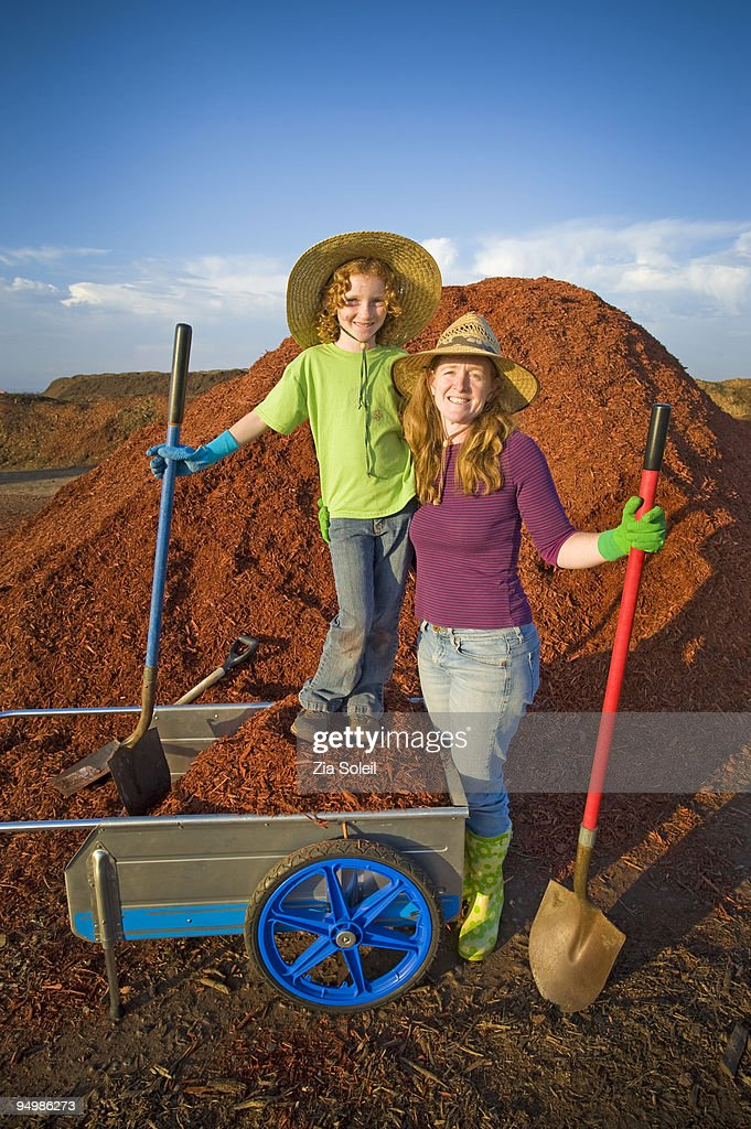 Mom & daughter loading mulch, municipal landfill : Stock Photo