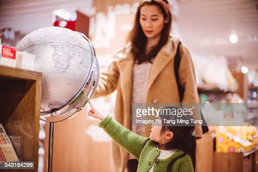 Mom & daughter looking at a model globe in shop