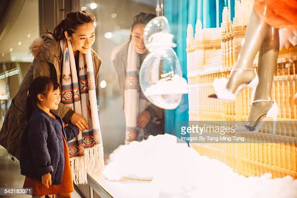 Mom & daughter looking at window display in mall