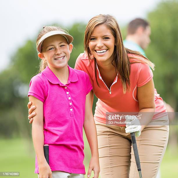 Mom & daughter playing golf together on course