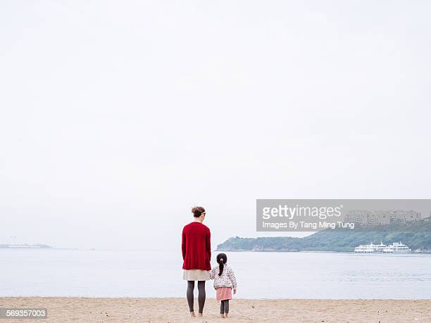 Mom & daughter standing on beach facing the sea