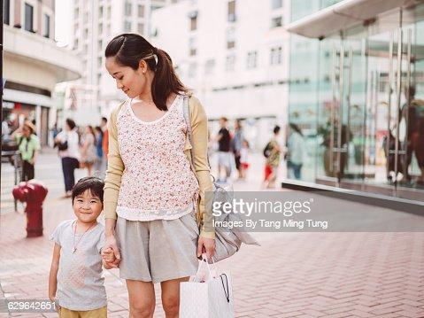 Mom & daughter strolling joyfully on street