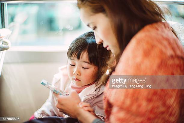Mom & daughter using smartphone on bus