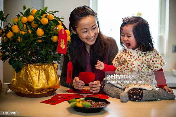 Mom decorating CNY tangerine tree with toddler