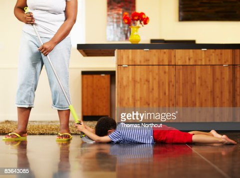 mom dragging boy across floor with broom : Stock Photo