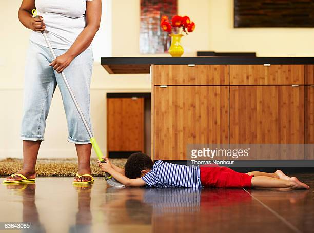 mom dragging boy across floor with broom