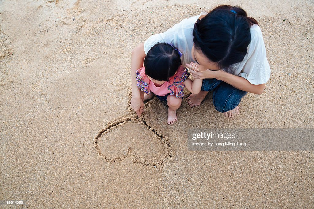 Mom drawing a heart in the sand with toddler girl : Stock Photo
