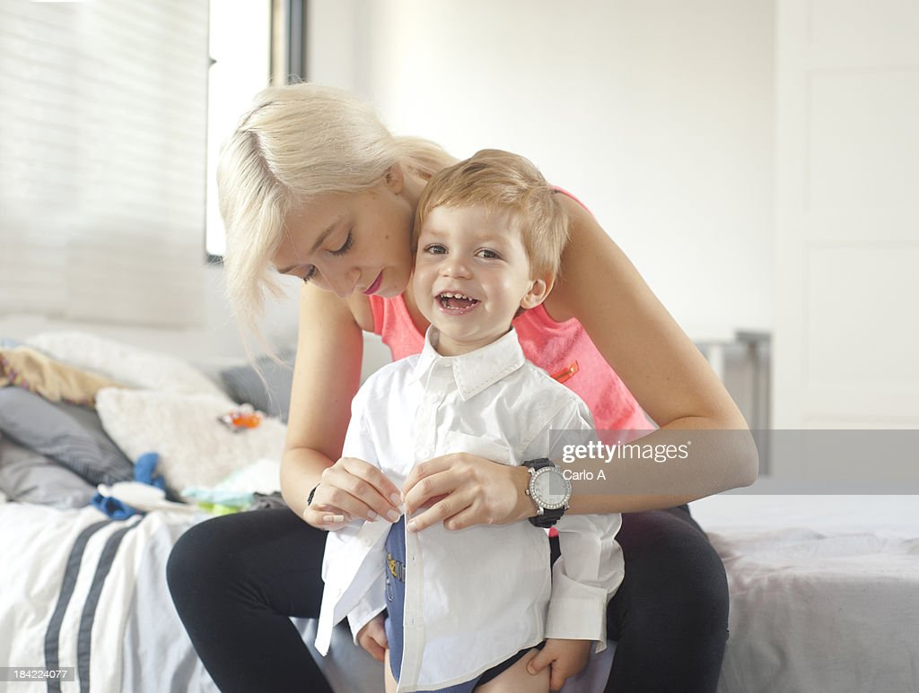 Mom  dressing her baby boy : Stock Photo