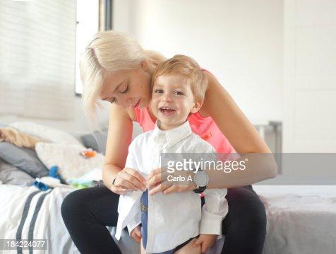 Mom  dressing her baby boy : Stock Photo