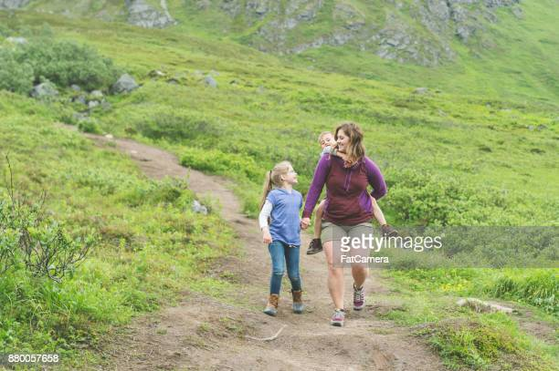A mom enjoys a leisurely hiking adventure with her two children in Alaska