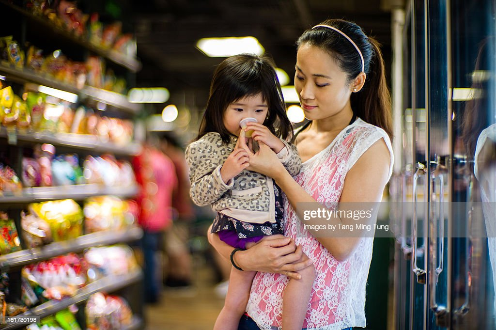 Mom feeding toddler with drink in supermarket : Stock Photo