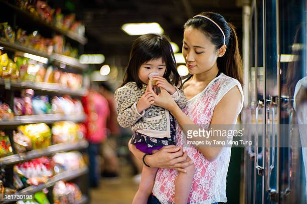 Mom feeding toddler with drink in supermarket