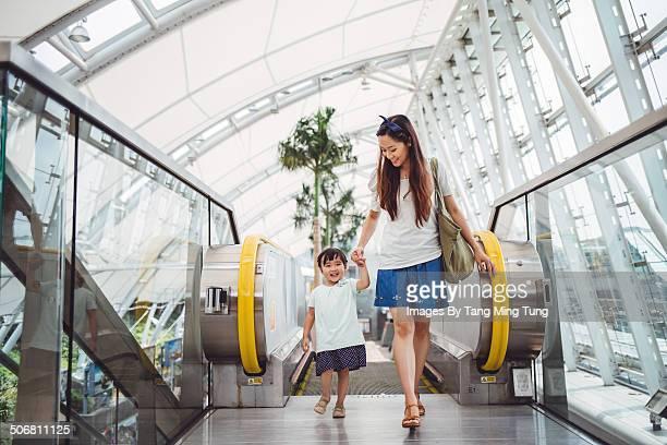 Mom going up escalator with child joyfully