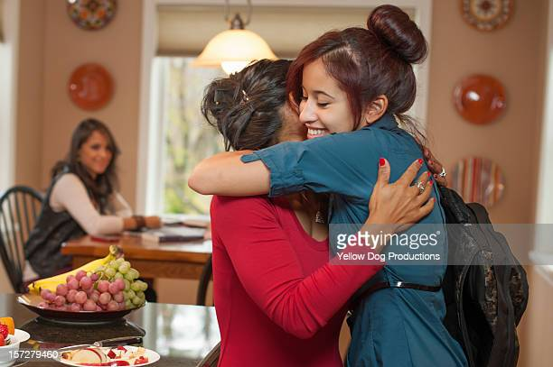 Mom greeting daughter after school in kitchen